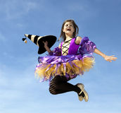 Happy Little Witch Jumping at the Blue Sky Royalty Free Stock Photography