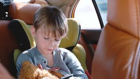 Happy little 4-6 year old European boy using smartphone entertainment app in car child safety seat during day ride. Happy little 4-6 year old European boy using stock footage
