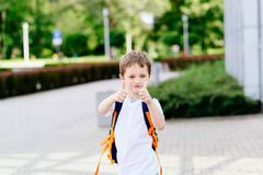 Happy little 7 years schoolboy showing thumbs up Royalty Free Stock Photo