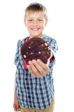 Happy little young boy holding choco chip cookie. Portrait of a happy little young boy holding choco chip cookie close to camera Stock Photos