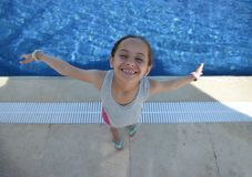 Happy Little Young Girl By Swimming Pool with Open Arms stock photo