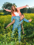 Happy lively young couple riding piggy back stock image