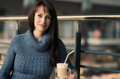 Happy woman drinking coffee in cafe. Happy lonely woman drinking coffee in cafe Stock Photography