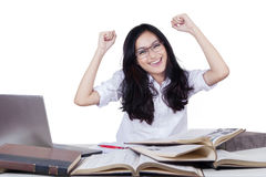 Happy long hair student raising hands. Portrait of carefree high school student with long hair, raising hands while studying with books and laptop Stock Photo