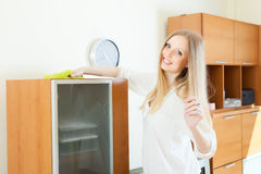 Happy long-haired housewife cleaning furniture. At home stock photography