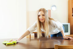 Happy long-haired housewife cleaning table Royalty Free Stock Images