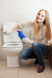 Happy long-haired housewife cleaning toilet bowl Royalty Free Stock Image