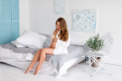Happy long haired pregnant woman in white greek style bedroom interior Royalty Free Stock Image