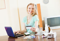 Happy long-haired woman buying drugs online. With laptop and credit card at home Royalty Free Stock Images