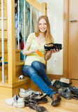Happy long-haired woman cleaning shoes Royalty Free Stock Image