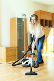 Happy long-haired woman in headphones cleaning with vacuum clean Royalty Free Stock Images