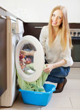 Happy long-haired woman loading clothes into  washing machine Royalty Free Stock Images