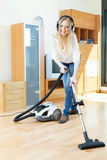 Happy long-haired woman  with vacuum cleaner Royalty Free Stock Photography