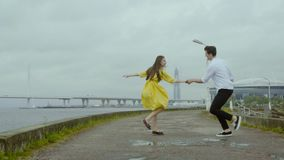 Amusing girl and boy dance emotionally some swift jive on rain pools of a pier stock video