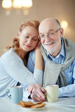Happy Long Marriage n. Portrait of smiling mature couple sitting close together embracing lovingly at kitchen table with tea cups and homemade cookies Royalty Free Stock Photography