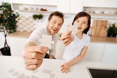 Happy-looking father and daughter showing jigsaw puzzle pieces Stock Image