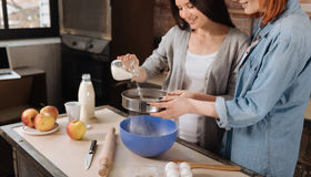 Happy looking female sieving flour Stock Images