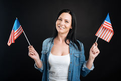 Happy looking girl holding American flags Royalty Free Stock Image