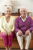 Happy Looking Senior Couple Sitting On Sofa At Home Stock Images