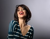 Happy loudly laughing with wide open mouth young woman with short hair in fashion sweater. portrait stock photography