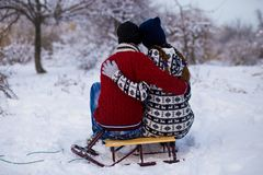 Happy love couple in bright clothes hugging in winter. Snow park Royalty Free Stock Photos