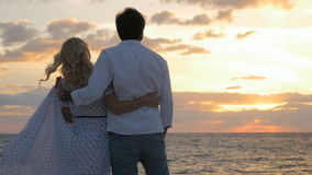 Happy in love couple enjoys a beautiful sunset on the beach stock footage