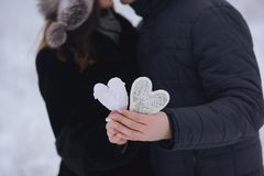 Happy love couple  in the forest in winter, walk, kiss, hug and hold  paper heart in park - Valentines Day Stock Image