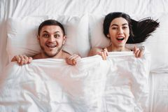 Happy love couple lies on big white bed, top view. Smiling intimate partners in bedroom, hot intimacy lovers Stock Image