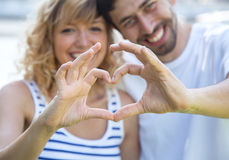Happy love couple outside showing heart with fingers. Outdoor on a sunny summer day Royalty Free Stock Image