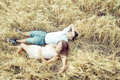 Happy in love couple relaxing on field Royalty Free Stock Photos