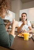 Happy love couple speaking at breakfast home Royalty Free Stock Photography