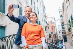 Happy in love couple take selfie photo on one of numerous bridges in Venice. Happy in love couple take selfie photo on one of numerous bridge in Venice, Italy royalty free stock images