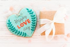 Happy love day text on cookie heart and craft gift box with gree. N ribbon on white rustic wooden background with confetti flat lay. happy valentine`s day Royalty Free Stock Photo