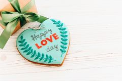 Happy love day text on cookie heart and craft gift box with gree. N ribbon on white rustic wooden background with confetti. space for text . mock-up happy Royalty Free Stock Image