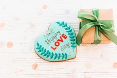 Happy love day text on cookie heart and craft gift box with gree. N ribbon on white rustic wooden background with confetti. space for text . mock-up happy Stock Photos