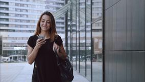 Happy and in love girl walks through the city with a phone. Happy girl walks through the city with a phone and smile stock footage