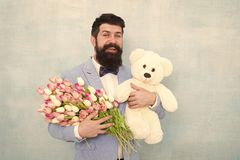 Happy and in love. Man bearded gentleman suit bow tie hold teddy bear and bouquet. Gentleman making romantic surprise