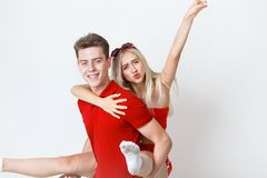 Happy lovely cheerful young couple in red casual look is hugging and smiling looking at camera on white background stock photography