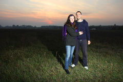 Happy lovely couple at sunset on meadow Stock Images