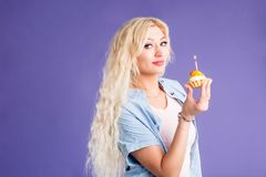 Happy lovely curly young woman holding birthday cupcake with candle royalty free stock photography