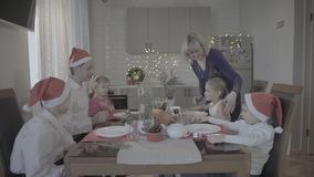 Happy lovely excited family of six celebrating Christmas dinner in festive atmosphere cozy kitchen. Happy lovely excited family of 6 celebrating Christmas dinner stock footage
