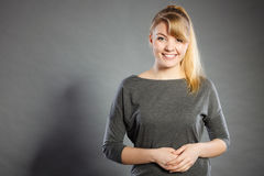 Happy lovely girl in grey. Charm and gladness. Blonde lovely girl in grey smiling. Happy glad charming female portrait stock photo
