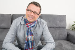 Happy and lovely man on sofa at home stock photos