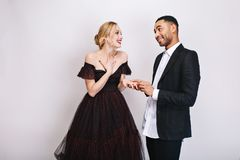Happy lovely moments of cute couple of handsome guy making proposal of marriage to beatiful blonde young woman in luxury. Happy lovely moments of cute couple of royalty free stock photo