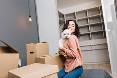 Happy lovely moments of joyful beautiful young woman with short curly brunette hair holding a little white dog in hands stock photography