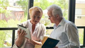 Happy lovely retired couple standing opposite each other with tablet and book. They smile.