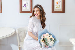 Happy lovely woman with bouquet of flowers sitting in cafe Royalty Free Stock Images