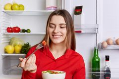 Happy lovely woman eats fresh vegetrian salad made with cucumbers and tomatoes, stands near opened fridge full of vegetables and f. Ruits, being vegan, doesn`t royalty free stock photography