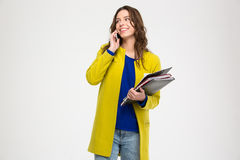 Happy lovely woman with folders talking on mobile phone Stock Image