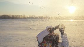 Happy lovely woman having fun and throwing the snow in winter field on sunset city background in slow motion with lense stock video footage